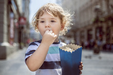 Little Boy Eating Popcorn In T...