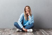 Happy Young Blonde Girl Sitting On A Floor