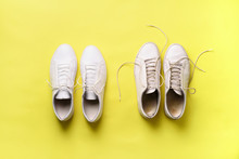 Old Dirty Sneakers Vs New White Sneakers On Yellow Background. Trendy Footwear. Top View. Concept Of Experience, Discipline And Chaos, Accuracy \ Mess, Stylish Shoes. Back To School