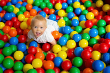 Cute Toddler Boy, Child, Playing In Colorful Balls In Children Playground