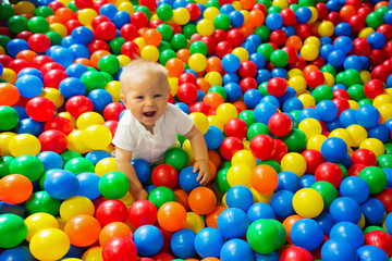 Fototapeta na wymiar Cute toddler boy, child, playing in colorful balls in children playground