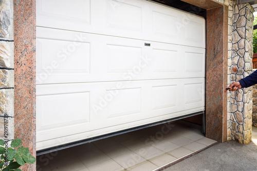 Fototapeta Garage door PVC. Hand use remote controller for closing and opening garage door obraz