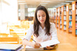 beautiful indian college girl reading a book in library (with selective focus and tone adjustment)