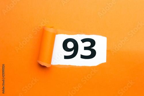 Fotografie, Obraz  Zahl dreiundneunzig - 93 verdeckt unter aufgerissenem orangen Papier