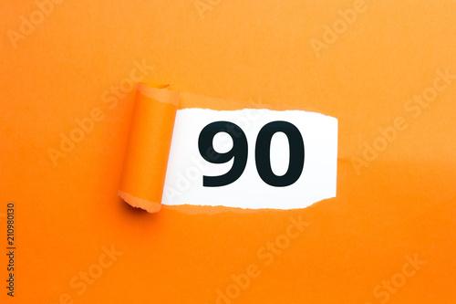 Valokuvatapetti Zahl neunzig - 90 verdeckt unter aufgerissenem orangen Papier