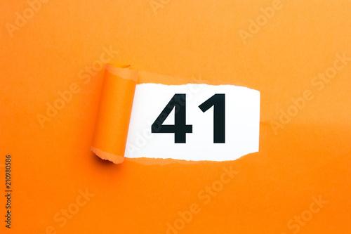 Fotografia  Zahl einundvierzig - 41 verdeckt unter aufgerissenem orangen Papier