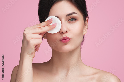 Fotografering  Beautiful woman with cotton pad in studio