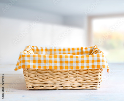 Foto Straw basket at kitchen table empty space.