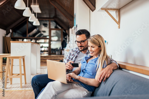 Obraz Couple shopping online while sitting on the sofa in modern apartment. - fototapety do salonu