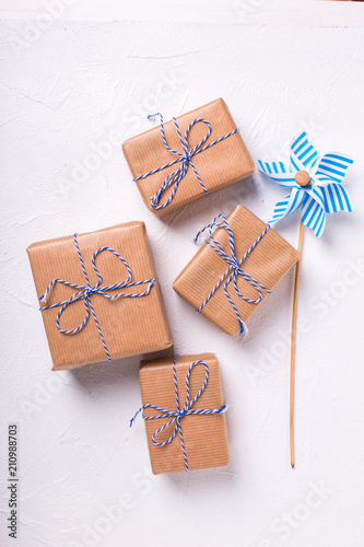 Festive gift boxes with presents and decorative windmill on textured white wooden background.