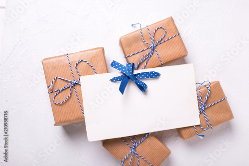Empty postcard and wrapped gift boxes with presents on textured background.