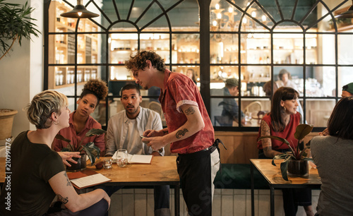 Waiter taking orders from customers sitting in a bistro Poster Mural XXL