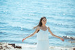 happy asian woman in white dress with wide arms standing by sea