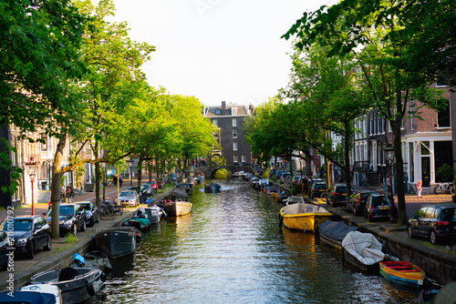 The center of a canal in Amsterdam with boats in cars Wallpaper Mural