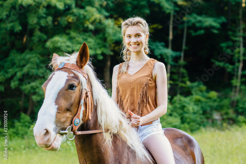 Tuinposter Ontspanning Sensuality elegance woman cowgirl, riding a brown horse. Clothed white jeans shorts, brown leather vest. Has slim sport body. Portrait nature. People and animals.