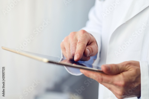 Male doctor working on a digital tablet near a window