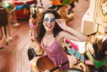 Smiling Lady With Dark Curly Hair In Sunglasses And Dress Standing With Lolly Pop Candy In Hand And Happily Looking In Camera While Riding On Carousel In Amusement Park