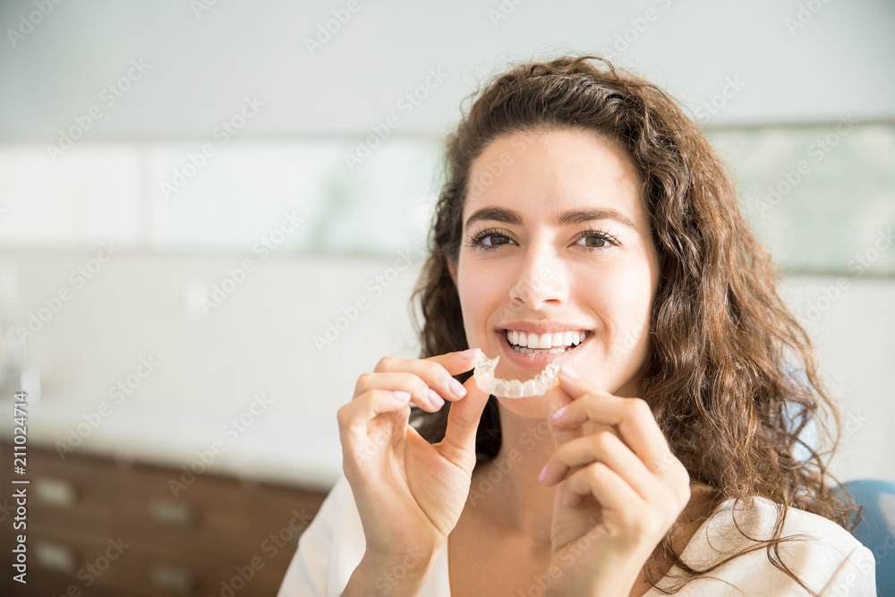 Fototapeta Beautiful Patient Holding Orthodontic Retainers In Dental Clinic