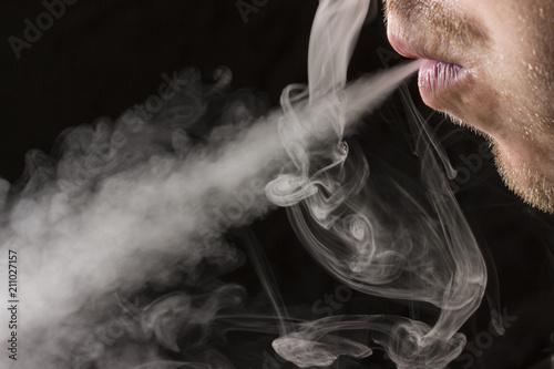 Fotografie, Obraz  man mouth exhales a stream of cigarette smoke