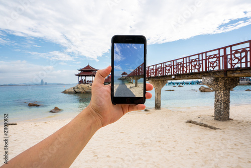 Crop tourist taking photo of beach
