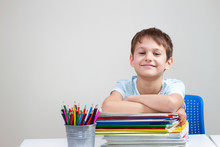 Smiling Boy With Colorful Books, Notebooks And Textbooks Sitting At The Table