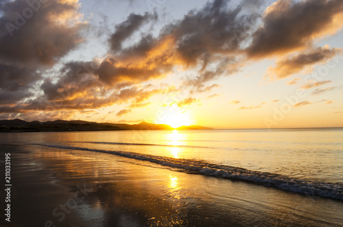 In de dag Ochtendgloren Yellow and orange sunrise on the beach with sun reflection on the wet sand and small wave on the calm ocean surface