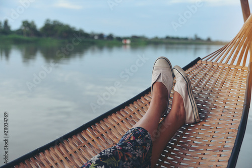 Poster de jardin Lieu connus d Asie Lifestyle of alone woman,feet of Hipster calm people sleeping and relaxing in hammock with nature background.Lifestyle and relaxing Concept.