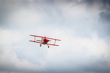 Red Propeller Airplane Flying Among The Clouds