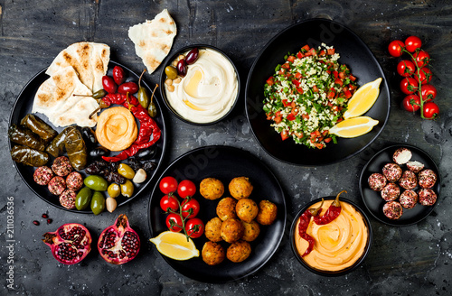 Photo Stands Ready meals Arabic traditional cuisine. Middle Eastern meze platter with pita, olives, hummus, stuffed dolma, labneh cheese balls in spices. Mediterranean appetizer party idea