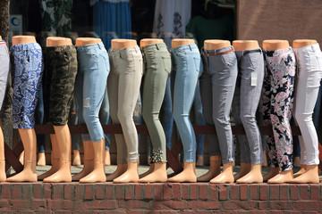 Różnej długości spodnie na nogach manekinów.