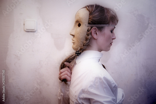 Blonde girl in a gray theatrical mask stands against the wall