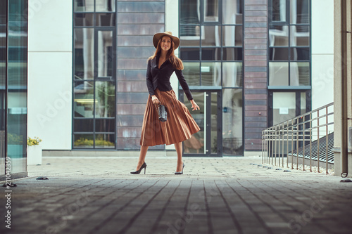 Fototapeta Happy fashion elegant woman wearing a black jacket, brown hat and skirt with a handbag clutch walking on the European city center