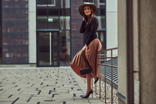 Smiling Fashion Elegant Woman Wearing A Black Jacket, Brown Hat And Skirt With A Handbag Clutch Posing While Leaning On A Steel Railing On The European City Center.
