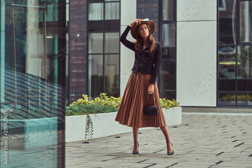 Photo Fashion elegant woman wearing a black jacket, brown hat and skirt with a handbag clutch walking on the European city center