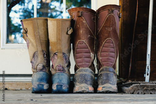 Fotografie, Obraz  His and hers dirty and mud covered snake hunting boots sitting on doorstep outside