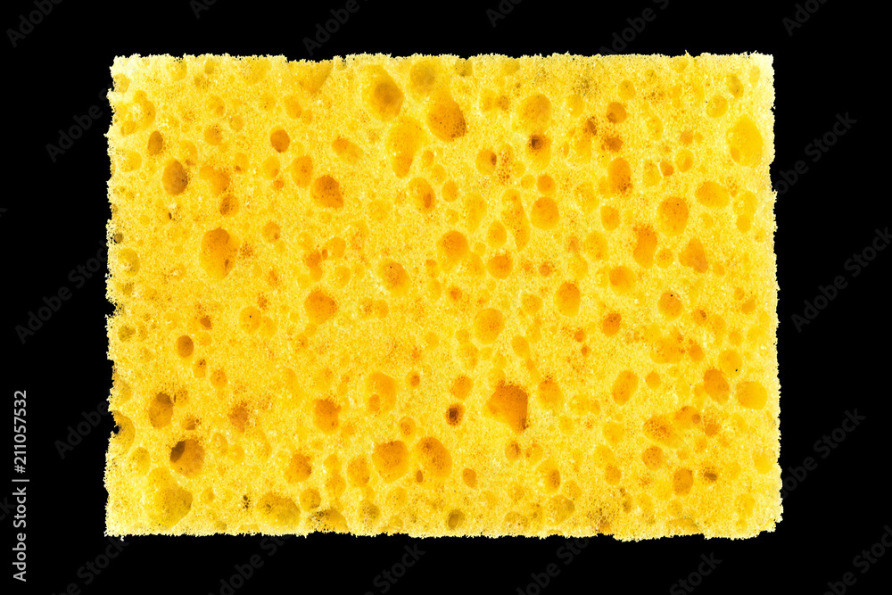 Fototapeta new yellow sponge for washing dishes on black background, abstract background