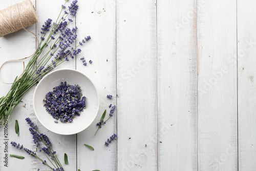 Lavender flowers on white wooden planks background, top view
