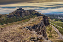 Beautiful Landscape Of Arthur's Seat Mountain In Scotland With Path On The Cliff And Edinburgh City In The Background