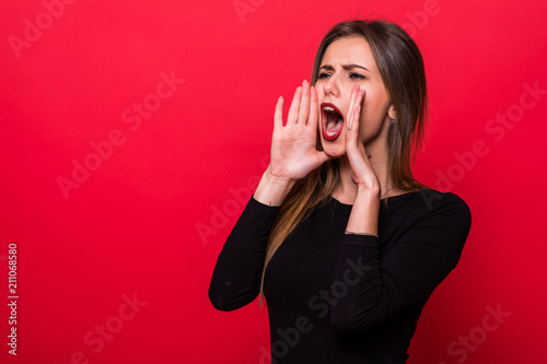 Slika na platnu Portrait woman shouting over red background