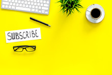 Email Subscribe Concept. Hand Lettering Subcribe On Work Desk With Plant, Glasses, Computer Keyboard, Cup Of Coffee On Yellow Background Top View Copy Space