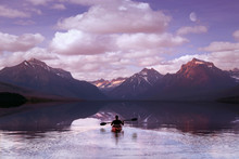 Adventurer Paddling On Mountain Lake During Morning Sunrise, With Beautiful Scenic Reflection Of Clouds And Sky