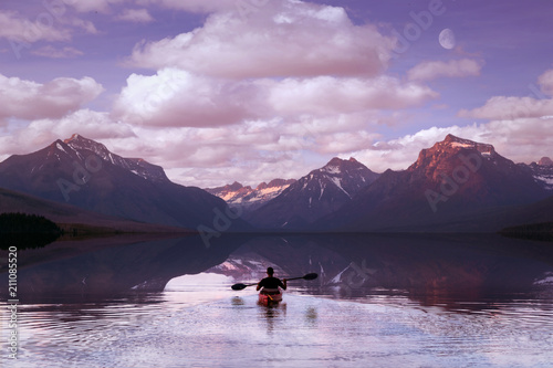 Valokuva  Adventurer paddling on mountain lake during morning sunrise, with beautiful scen