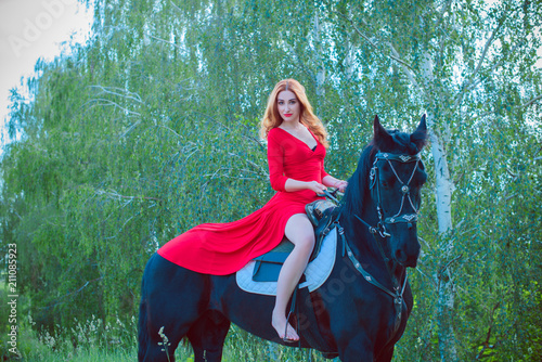 Beautiful young woman in long red dress riding a horse in countryside Wallpaper Mural