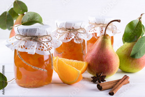 Crédence de cuisine en verre imprimé Eclaboussures d eau Pear and orange jam in glass jars with ripe pears, cinnamon sticks, anise stars and green leaves on the table.