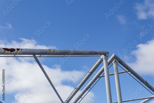 Fotografie, Obraz  Abstract background of overhead pipes against a blue sky with clouds, horizontal