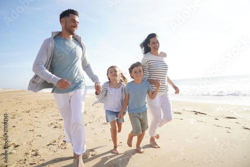 Fototapeta Family running on sandy beach at sunset obraz