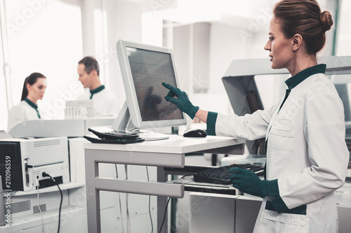Attention. Waist up of concentrated skilled laboratory assistant using computer and pointing at screen while searching patients records
