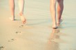 Closeup of a lady woman and man couple lover bare feet walking and footprint at wet on the beach romantic honeymoon. Vacation on ocean beach,foot on sea sand. Shadow from the sun hits the sand. travel