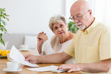 Elderly Couple Calculating Cos...