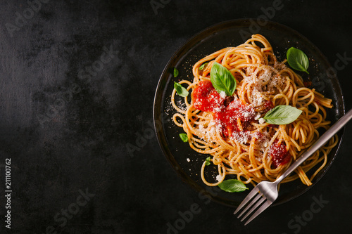 Fototapeta Dark plate with italian spaghetti on dark obraz